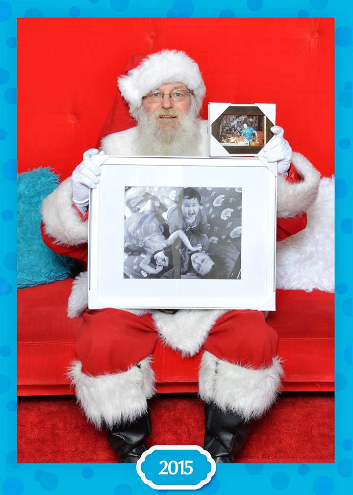 Santa Claus poses with a photograph of the Neville-Lake children and their grandfather.