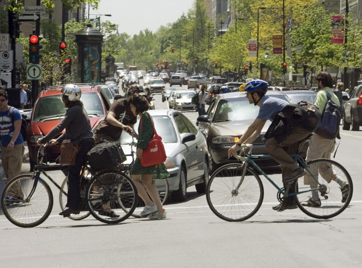 Pedestrians and cyclists cross Sherbrooke Street in downtown Montreal.