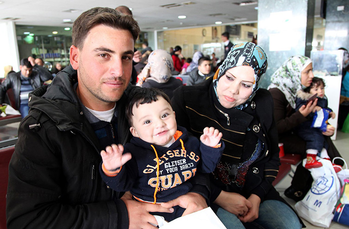Radi poses for a photo with his son and wife, who names are omitted for security reasons, while waiting in an airport in Amman, Jordan, to board a plane to Canada, Sunday, Dec. 20, 2015.