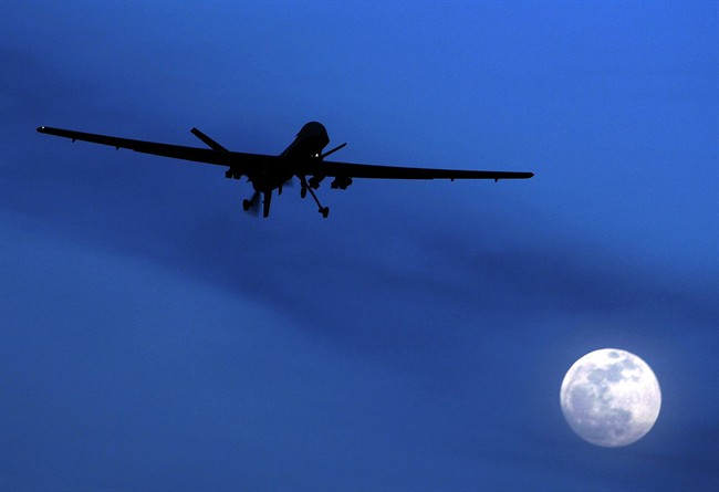 FILE - In this Jan. 31, 2010 file photo, an unmanned U.S. Predator drone flies over Kandahar Air Field, southern Afghanistan, on a moon-lit night.  (AP Photo/Kirsty Wigglesworth, File).