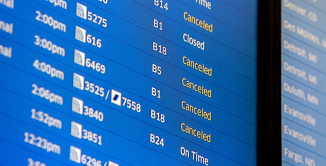 Flight boards at O'Hare International Airport show cancellations Friday, Jan. 22, 2016 in Chicago.
