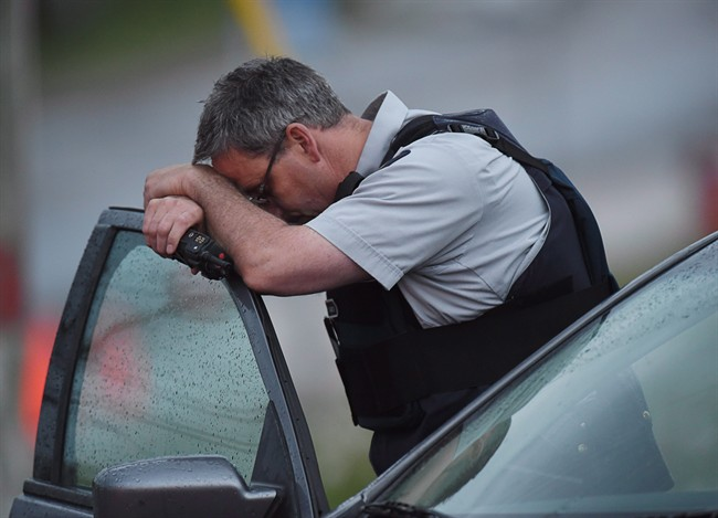 An RCMP officer rests his head at a roadblock in Moncton, N.B. on Thursday, June 5, 2014.