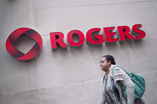 A pedestrian walks past the Rogers headquarters in Toronto.