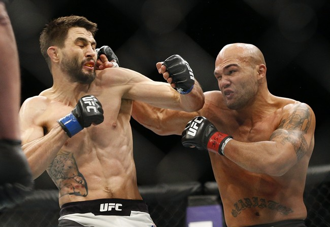 Robbie Lawler, right, hits Carlos Condit during a welterweight championship mixed martial arts bout at UFC 195, Saturday, Jan. 2, 2016, in Las Vegas. Lawler made a basic purse of US$500,000 for his hard-earned split-decision win over challenger Condit on Saturday at UFC 195.THE CANADIAN PRESS/AP/John Locher.