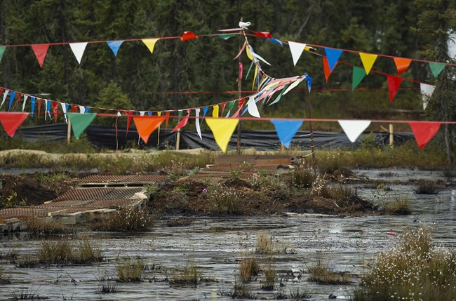Flags hung over a pipeline leak to keep birds away as crews work to contain and clean up a pipeline spill at Nexen Energy's Long Lake facility, near Fort McMurray, Alta., on July 22, 2015.