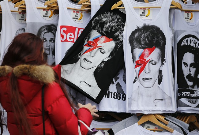 A woman looks at shirts with a portrait of David Bowie, in London, Monday, Jan. 11, 2016.