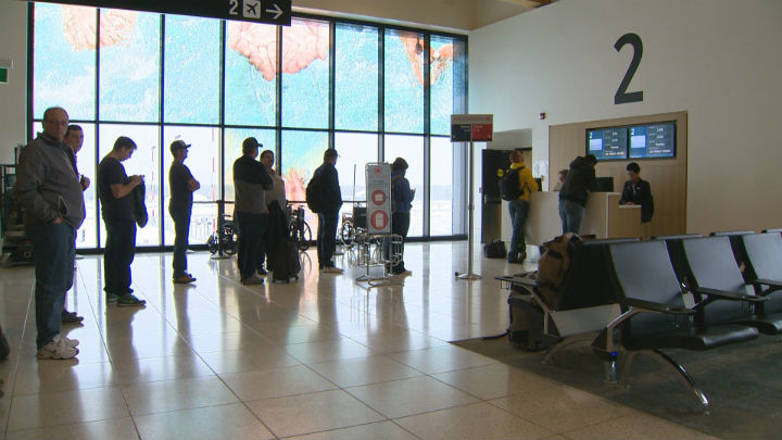 Passengers line up for a flight to Toronto at the airport in Fort McMurray, Alberta.