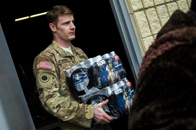 Michigan National Guard Staff Sgt. Stephen Robel helps carry a case of water to the vehicle of Flint resident Karand Houston.