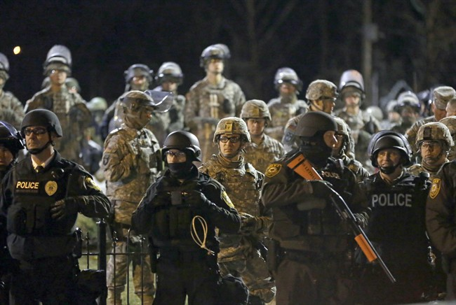 In this Friday, Nov. 28, 2014, file photo, police and Missouri National Guardsmen face protesters gathered in front of the Ferguson Police Department in Ferguson, Mo.