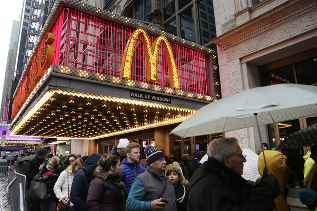pedestrians pass under a McDonald's marquee in New York.