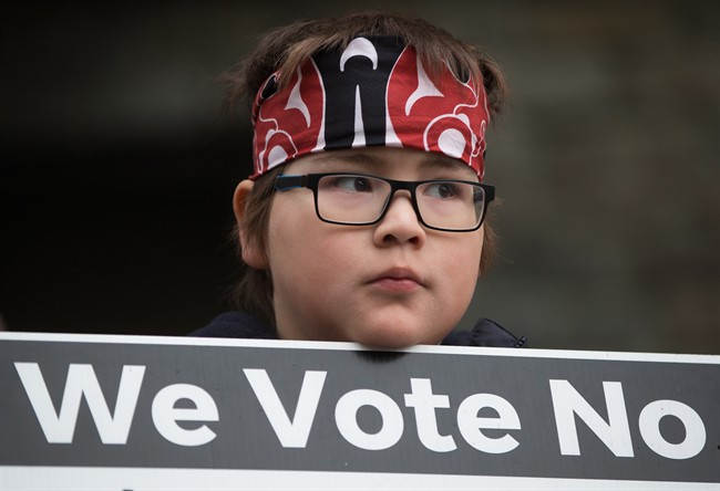 Jamie Antone, 9, of the Squamish First Nation, holds a sign as protesters gather outside National Energy Board hearings on the proposed Trans Mountain pipeline expansion in Burnaby, B.C., on Tuesday January 19, 2016.