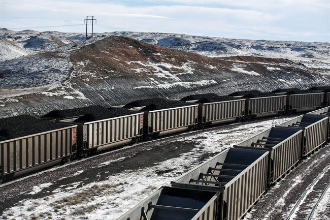 FILE - In this Jan. 9, 2014, file photo, rail cars are filled with coal and sprayed with a topper agent to suppress dust at Cloud Peak Energy's Antelope Mine north of Douglas, Wyo.