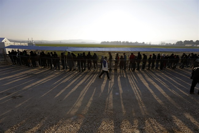 People form a line as they wait to receive food distributed by non-governmental organizations at a refugee camp in the northern Greek village of Idomeni Thursday, Jan. 21, 2016. About 1,000 refugees from Syria, Afghanistan and Iraq are stranded at Greece's northern border with Macedonia, after Macedonian authorities stopped letting them through citing problems with transit flows further north on the Balkan route which have caused a chain reaction. (AP Photo/Thanassis Stavrakis).