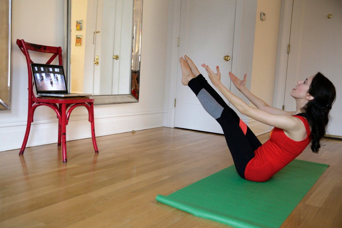 In this April 14, 2015 photo, Christina Macchiarola demonstrates how she uses the Crunch Live fitness app to work out in her apartment in New York. Crunch Live includes many of the workouts that earned the brand a devoted following and have been retired from their brick and mortar gyms.