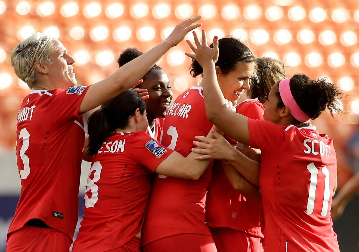 Canada's Christine Sinclair, center, is congratulated after scoring a goal against Trinidad & Tobago during the second half of a CONCACAF Olympic qualifying tournament soccer match Sunday, Feb. 14, 2016, in Houston. Canada won 6-0.