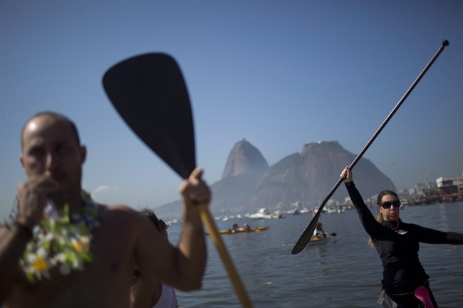 Protesters hold up paddles and whistle during a demonstration on Botafogo Beach, in the Guanabara Bay in Rio de Janeiro, Brazil, on June 6, 2015, near where Olympic sailing events are to be held.