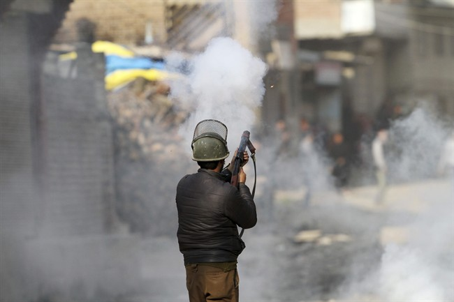 An Indian policeman fires tear smoke shell on protesters during a clash in Srinagar, Indian controlled Kashmir, Monday, Feb. 15, 2016.
