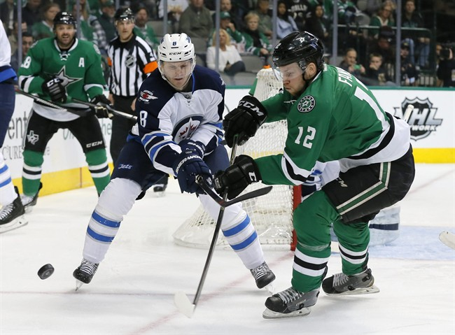 Winnipeg Jets' Jacob Trouba and Dallas Stars' Radek Faksa compete for control of the puck in the first period of an NHL hockey game on Feb. 25, 2016.