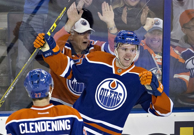 Edmonton Oilers' Connor McDavid (97) and Adam Clendening (27) celebrate McDavid's goal against the Columbus Blue Jackets during second period NHL action in Edmonton, Alta., on Tuesday February 2, 2016.