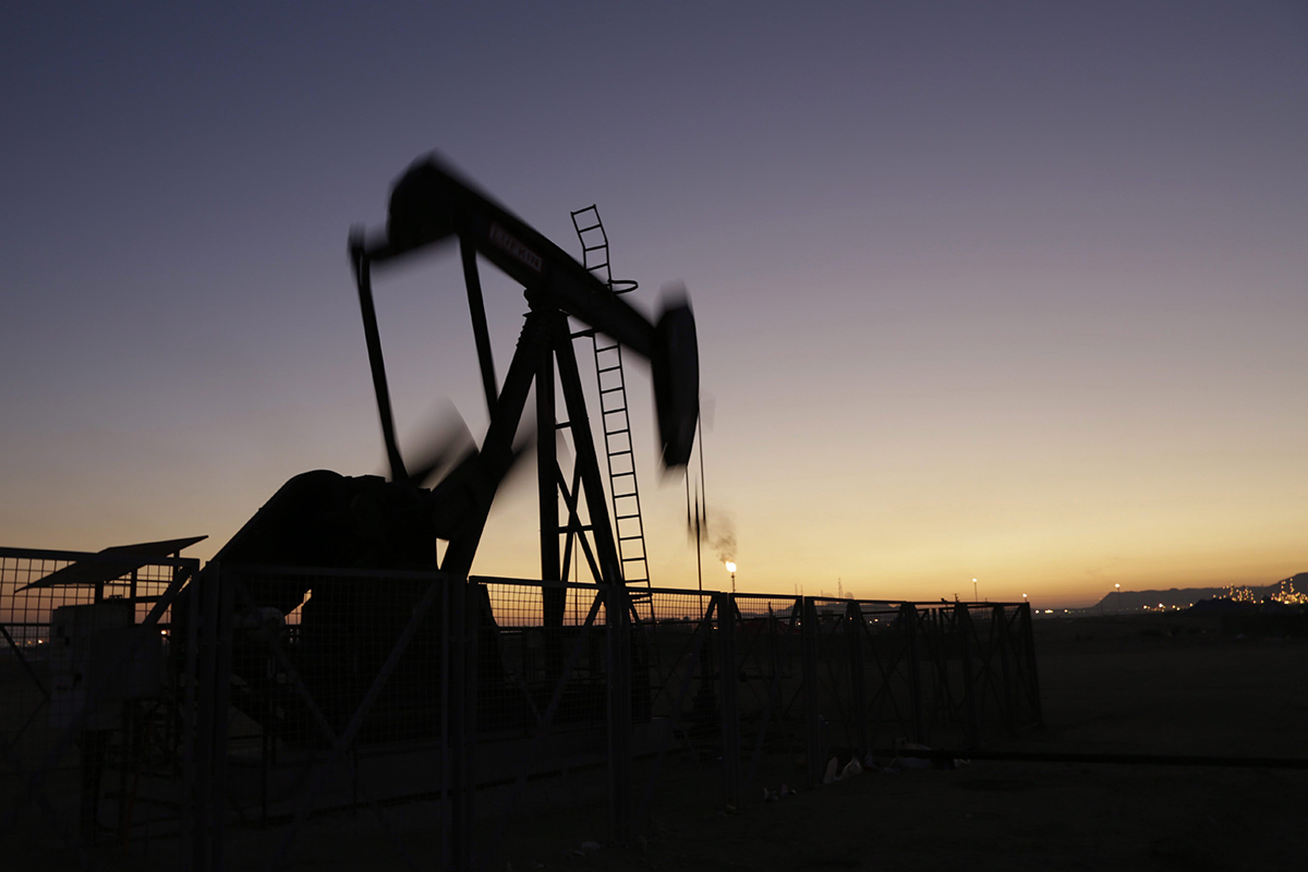 An oil pump works at sunset.