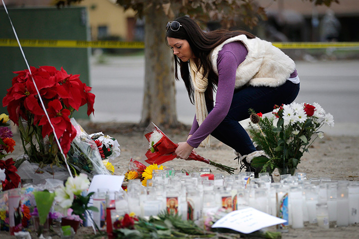 Jennifer Caballero places flowers at a makeshift memorial honouring the victims of the San Bernardino shooting rampage, Friday, Dec. 4, 2015, in California.