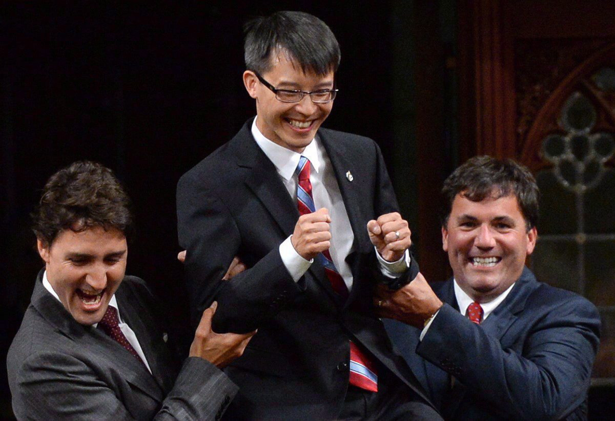 Liberal Leader Justin Trudeau and MP Dominic LeBlanc, right, escort new Liberal MP Arnold Chan in the House of Commons on Parliament Hill in Ottawa on Sept. 15, 2014.