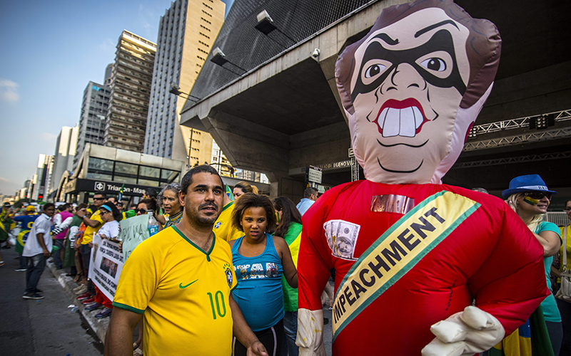 Protesters stand next to a balloon with the effigy of President Dilma Rousseff on March 19 2016. Brazilian lawmakers relaunched impeachment proceedings against Rousseff and a judge blocked her bid to bring her powerful predecessor into her cabinet, intensifying the political crisis engulfing her.