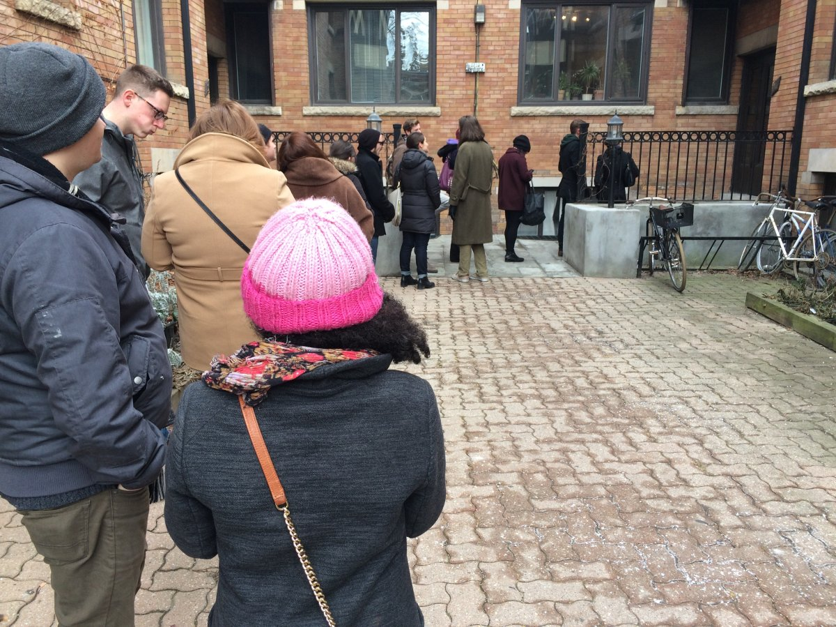 Graham Post and Alexis Gabrielle stand in a long line, waiting to view a Toronto apartment rental.