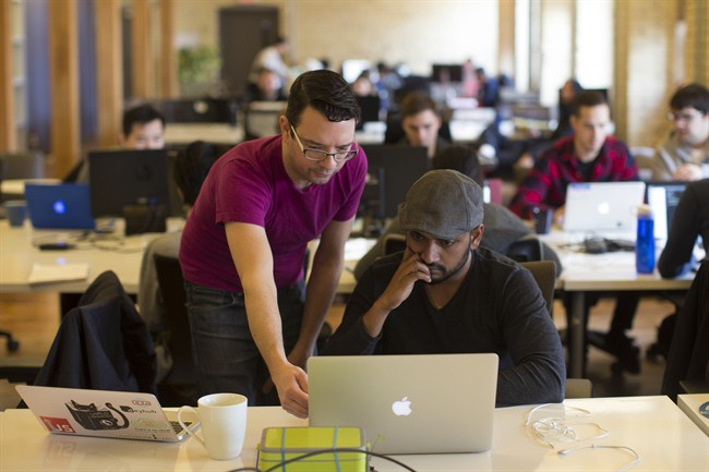 A tutor helps a student at Lighthouse Labs, which offers bootcamps on coding, in Toronto on Thursday, March 17, 2016.