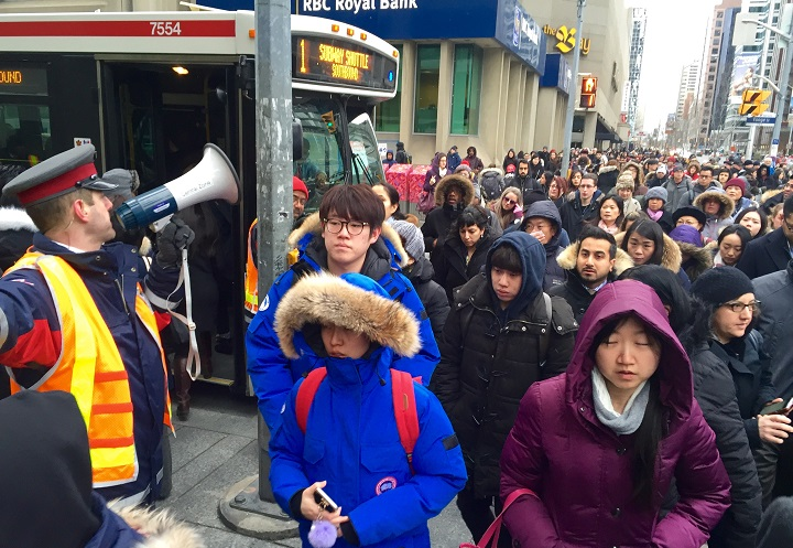 TTC commuters wait for shuttle buses due to a major subway and streetcar disruption on March, 1, 2016.