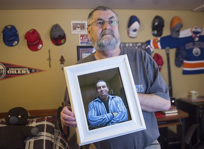Ernie LeBlanc hold a photo of his son Jason LeBlanc at their home in Sydney Mines, N.s. on Monday, March 14, 2016.