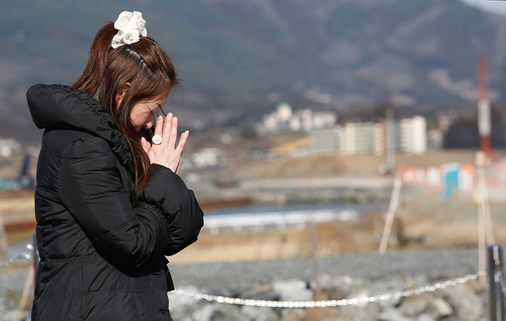A woman prays in front of the lone pine tree that miraculously survived the deadly 2011 earthquake and tsunami among 70,000 trees along the coastline in Rikuzentakata, northeastern Japan, Friday March 11, 2016.