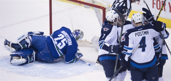 The Winnipeg Jets celebrate teammate Marko Dano's goal past Vancouver Canucks goalie Jacob Markstrom (25) during third period NHL action in Vancouver on Monday, March 14, 2016.
