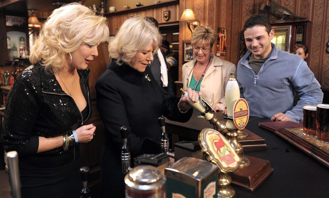 FILE - In this Thursday, Feb. 4, 2010 file photo, the Duchess of Cornwall, second left, pulls a pint of beer in the Rovers Return pub, as she meets actors Beverley Callard, left, who plays landlady Liz McDonald, Anne Kirkbride, second right, who plays Deirdre Barlow, second right, and Ryan Thomas, who plays Jason Grimshaw, during a visit to the the set of the British television soap opera 'Coronation Street', in Manchester, England.