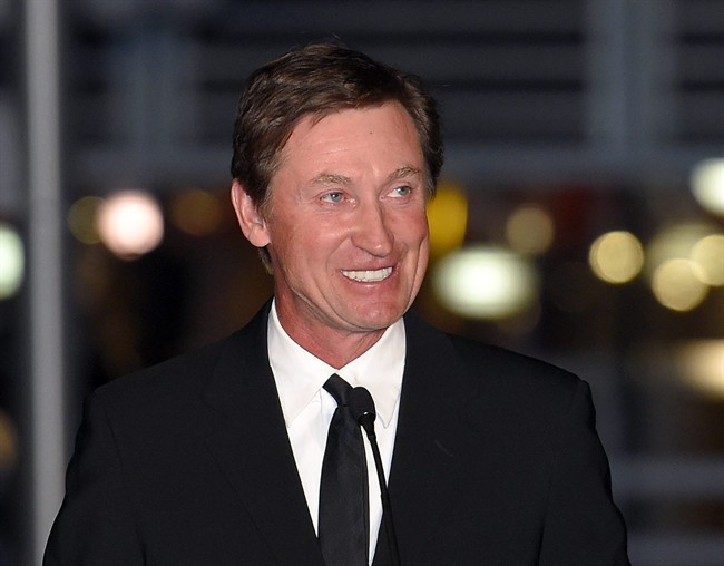In this March 7, 2015 file photo, former Kings player Wayne Gretzky speaks to the crowd at a statue unveiling for former Kings left wing Luc Robitaille prior to an NHL hockey game against the Pittsburgh Penguins in Los Angeles. Gretzky, the NHL's all-time scoring champion, has a deal with G.P. Putnam's Sons for a book about the game's history and his own place in it.