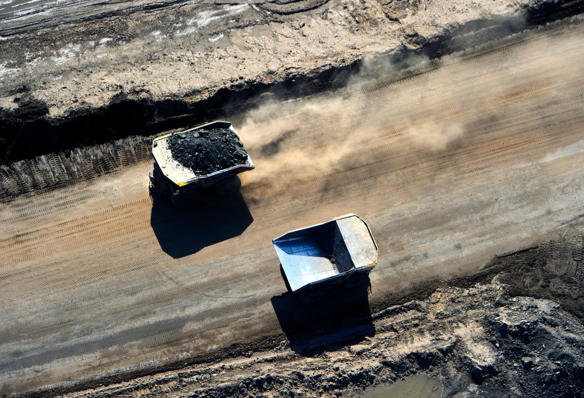 Huge Caterpillar 797 dump trucks working at the CNRL (Canadian Natural Resources Limited) Horizon oil sands mine near Fort McMurray, Alberta.