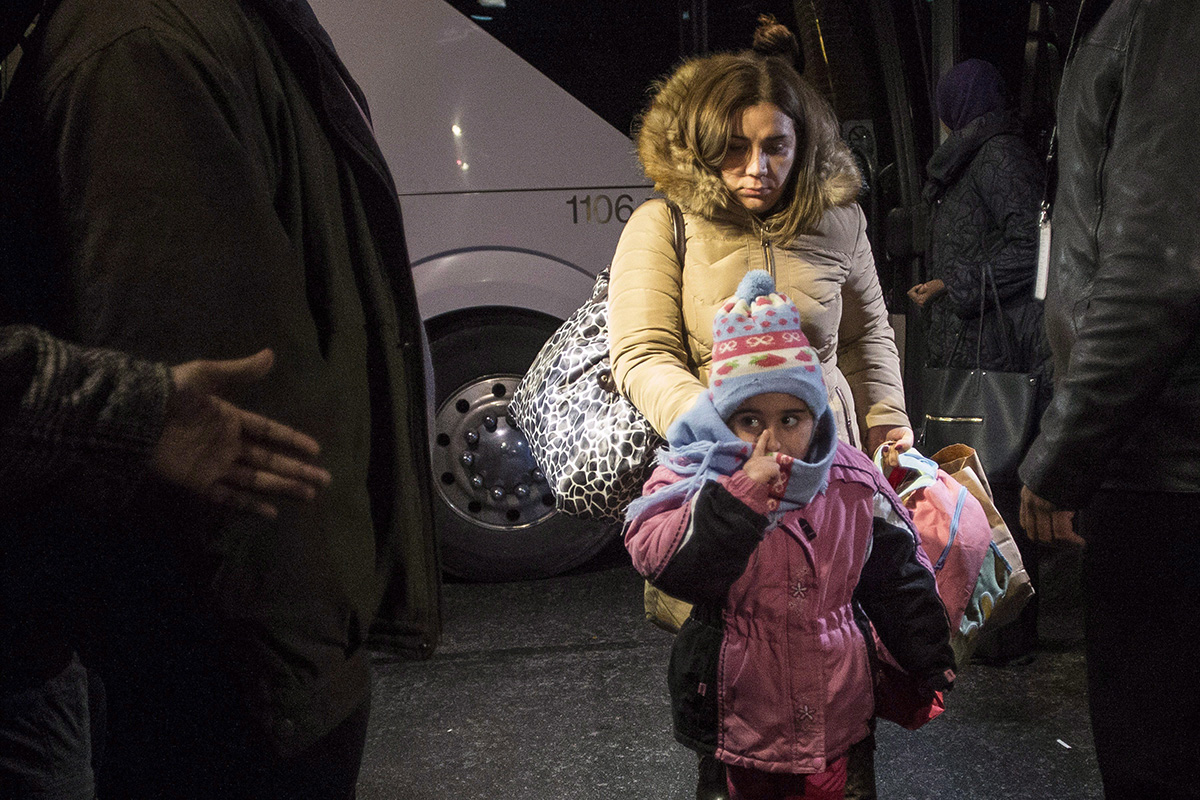 Syrian refugees step off a bus into a hotel after arriving on the first government-arranged flight into Toronto's Pearson Airport, on Friday, Dec. 11, 2015.