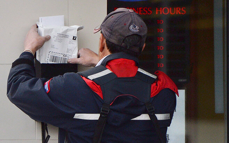 A mail carrier delivers mail in Ottawa, on Dec.11, 2013.