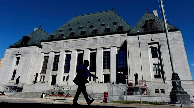 A pedestrian walks past the Supreme Court of Canada in Ottawa on Thursday, July 23, 2015.