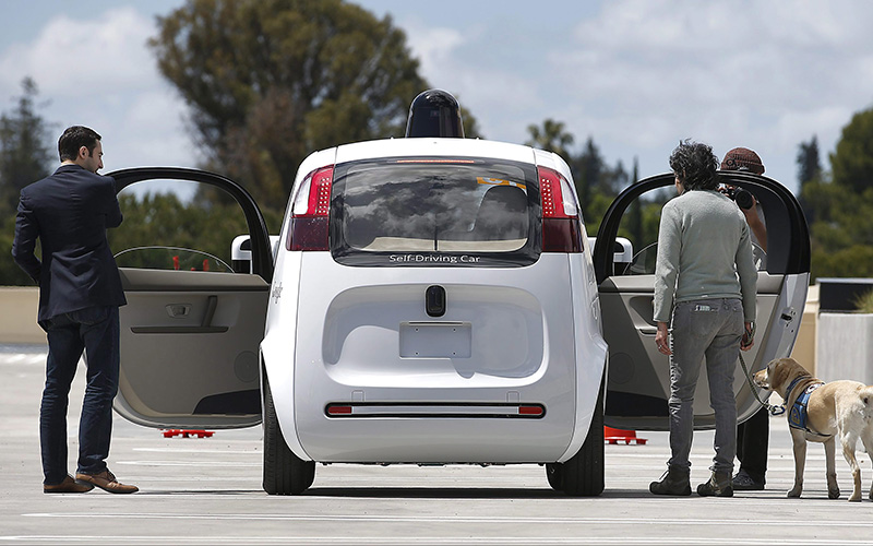 Riders enter the Google's new self-driving prototype car for a ride during a demonstration at Google campus on Wednesday, May 13, 2015, in Mountain View, Calif.