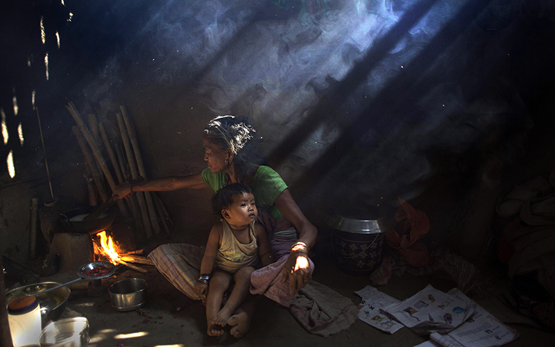 An elderly Indian woman cooks using firewood at her home at Gobhali village on the outskirts of Gauhati, India.