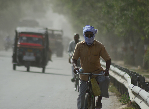 Indian commuters move on the side fringes of a busy road,  in a heavy dust strom and killer heat waves , during a hot day in Allahabad on April 12,2016. (Photo by Ritesh Shukla/NurPhoto via Getty Images).