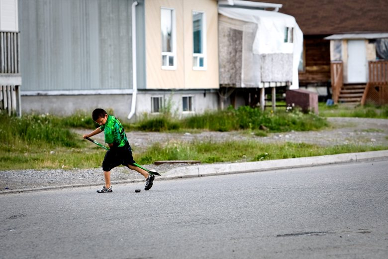 A young First Nations child plays street hockey, July 17, 2009.