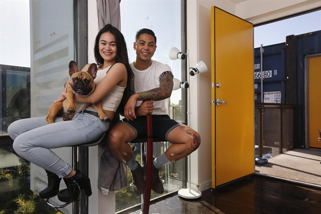 Patrick Tupas, right, with his wife, Maria Real-Tupas, who is holding their dog Moon Moon Fitzgerald, sit in the living room at their shipping container apartment in Phoenix.