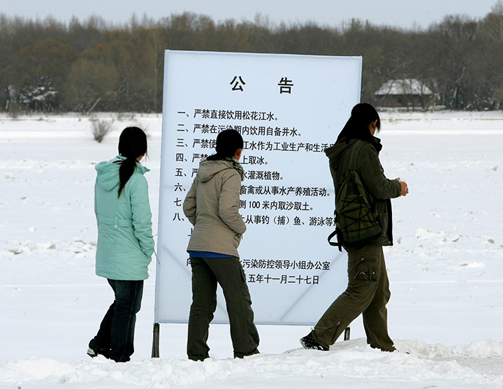Locals stop to read a sign warning about toxic pollution in the frozen Songhua River, on the bank of the river in Jiamusi, in China's northeast Heilongjiang province Monday Dec. 5, 2005.