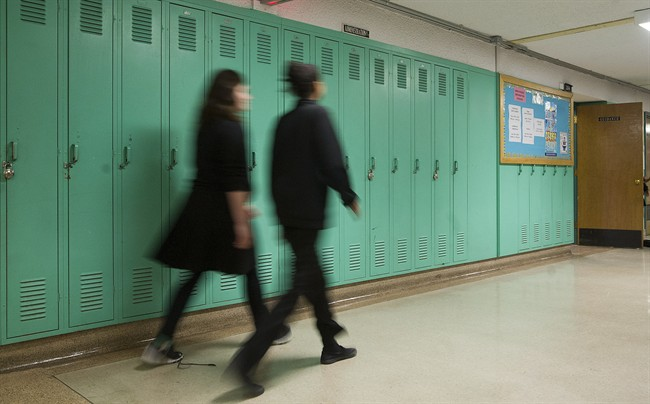 Students walk by lockers in a Montreal school.