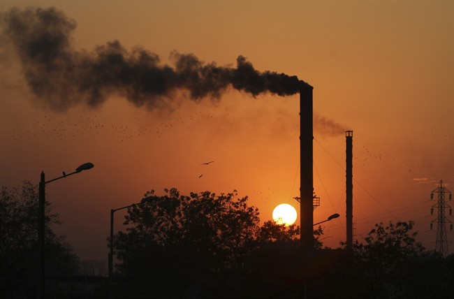 This is 2014 file photo of birds as they fly past at sun set as smoke emits from a chimney at a factory in Ahmadabad, India.