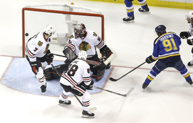 St. Louis Blues' Vladimir Tarasenko (91), of Russia, watches as a puck slips past Chicago Blackhawks goalie Corey Crawford, Brent Seabrook (7) and Patrick Kane (88) during the first period in Game 7 of an NHL hockey first-round Stanley Cup playoff series Monday, April 25, 2016, in St. Louis.