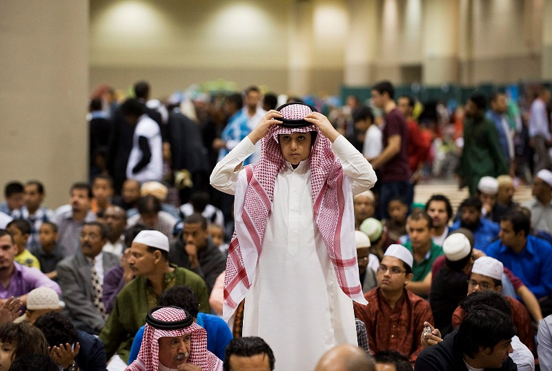 A boy puts on his head dress at the Muslim Association of Canada's Eid celebration that marks the end of the holiday of Ramadan at the Metro Convention Centre in Toronto on Tuesday, August 30, 2011.