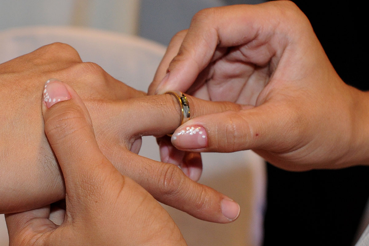 A bride places a wedding band on the finger of her soon-to-be husband.